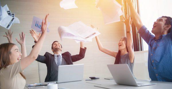 Blije zakenmensen zittend achter laptops die papieren facturen in de lucht gooien
