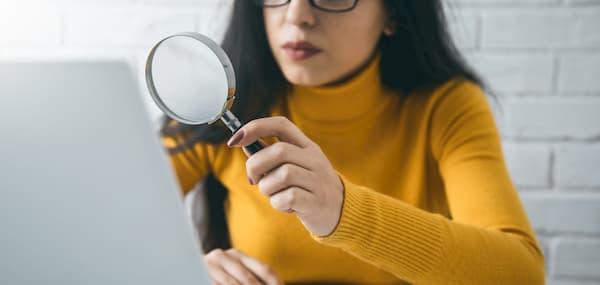 Vrouw achter computer met vergrootglas bekijkt gescande facturen met loep voor Exact Online