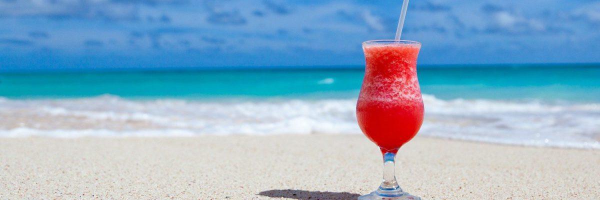 Cocktail op het strand om vakantie uit te beelden waarbij je eenvoudig facturen kunt goedkeuren met TriFact365.