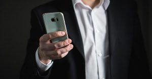 man met smartphone in de hand werkt met de TriFact365 app en gaat bonnetjes scannen om te declareren.