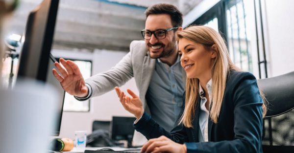 Man en vrouw achter de computer die vrolijk kijken naar voordelen van TriFact365