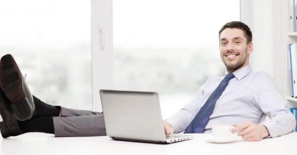 Blije man achter computer met benen op tafel werkt met Scan & Herken software