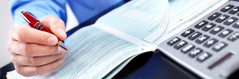 hand met pen en rekenmachine met bankafschriften
