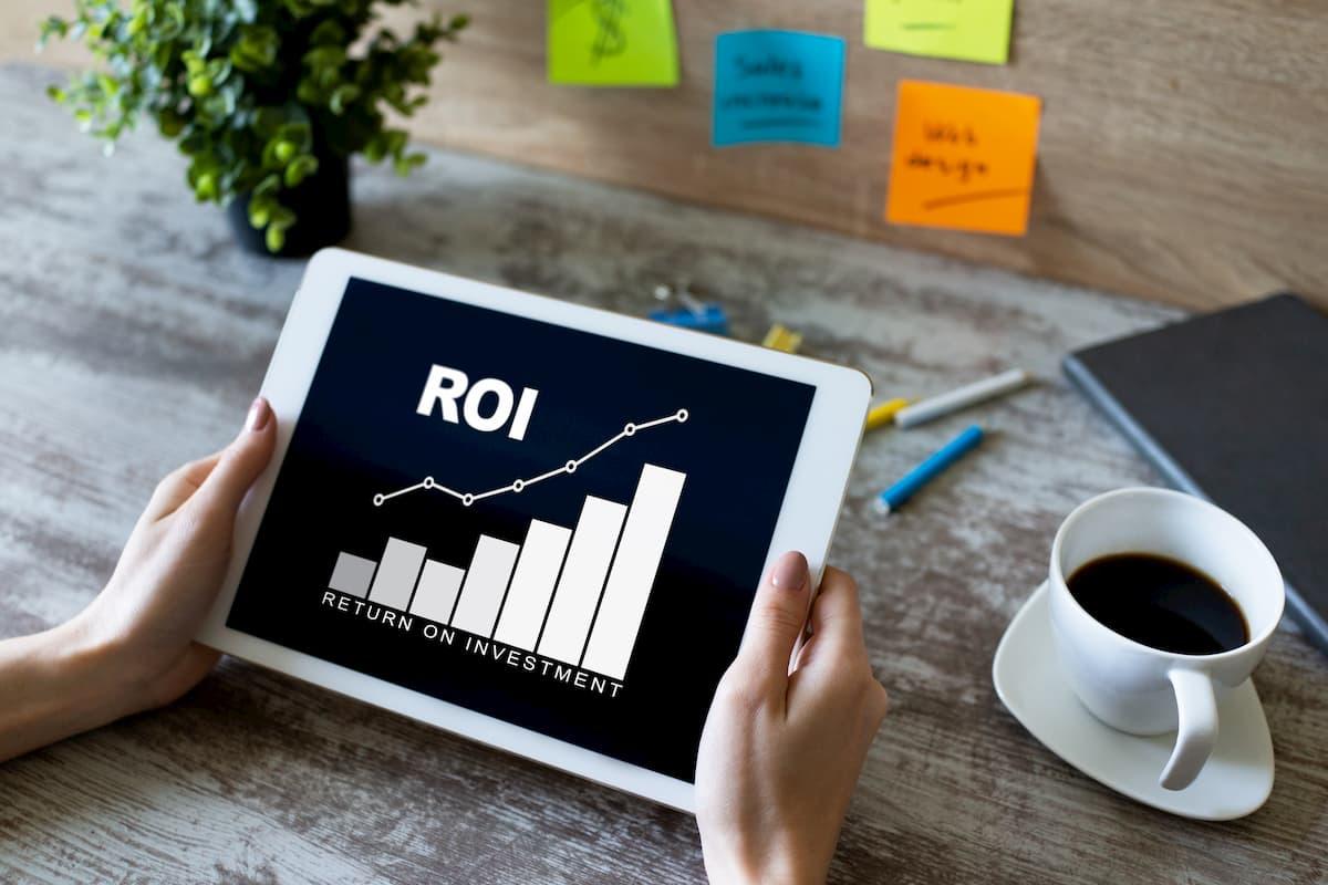 Bureau met kop koffie en tablet waarop ROI (return on investment) staat vermeld.
