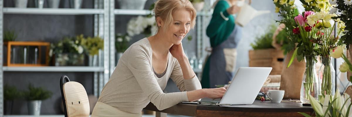 Une femme est assise à une table sur laquelle se trouve un vase de fleurs et regarde joyeusement son ordinateur portable pour comparer les logiciels de numérisation et de reconnaissance.