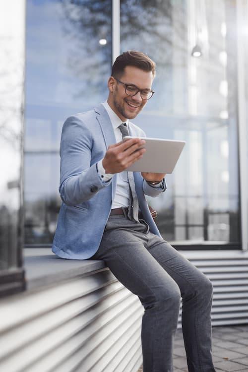 Un homme en veste et cravate regarde une tablette pour le logiciel Scan & Recognise.